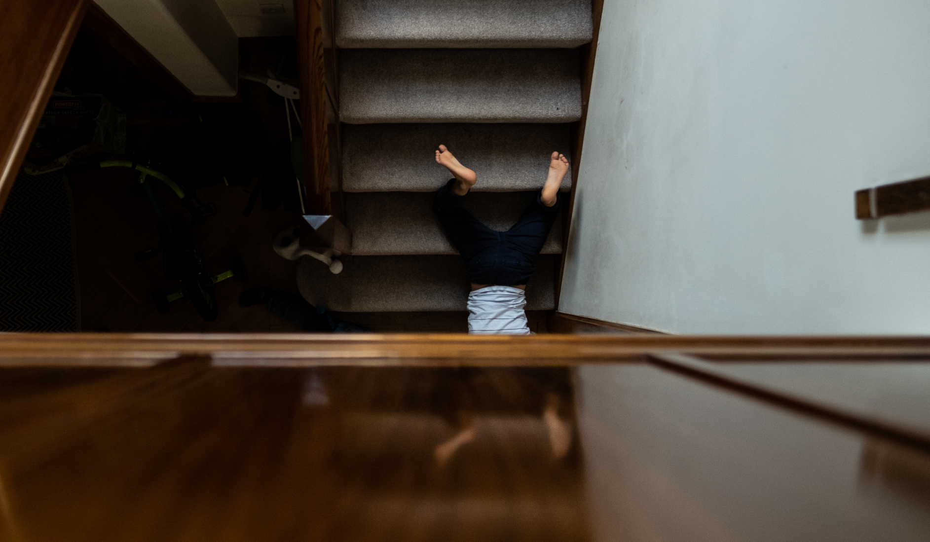 little boy's feet up on stairs giving the impression that he is falling down the stairs