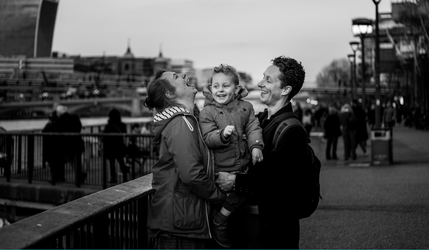 family of three laughing while being photographed by London family photographer ralu chase
