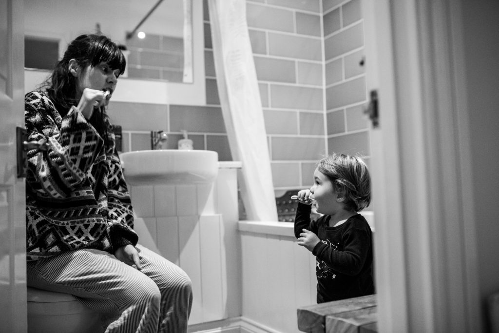 mom and son brushing teeth in the morning. the little boy mirrors what the mom does. Cotswolds, UK. Cotswolds Family Photographer