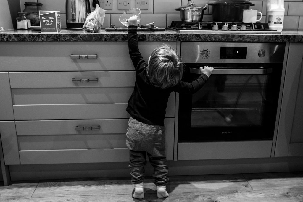 little boy reaching to the top of the counter ready to drag down a glass bowl with food in it. the photo is captured by a Cotswolds family photographer, kalura photography