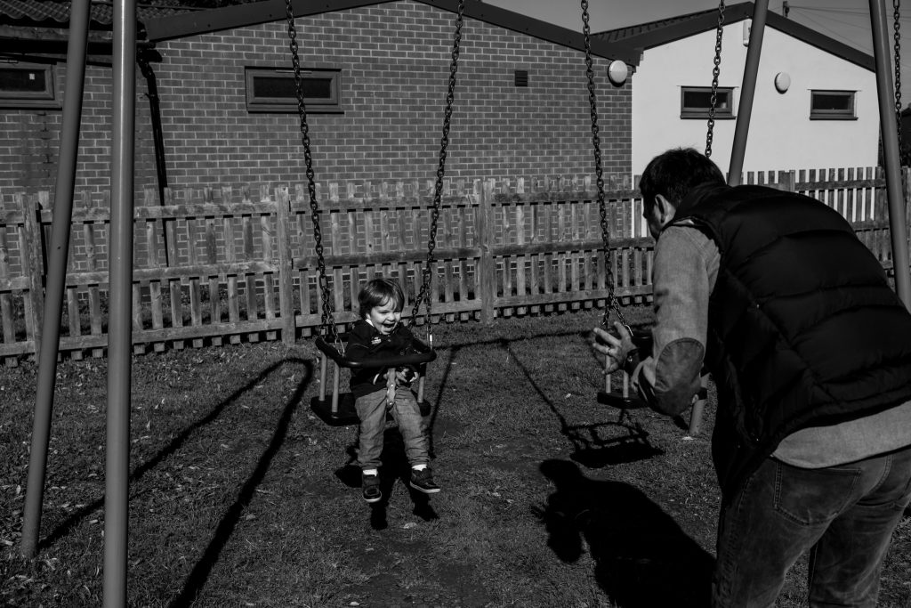 little boy in the swing laughing at dad