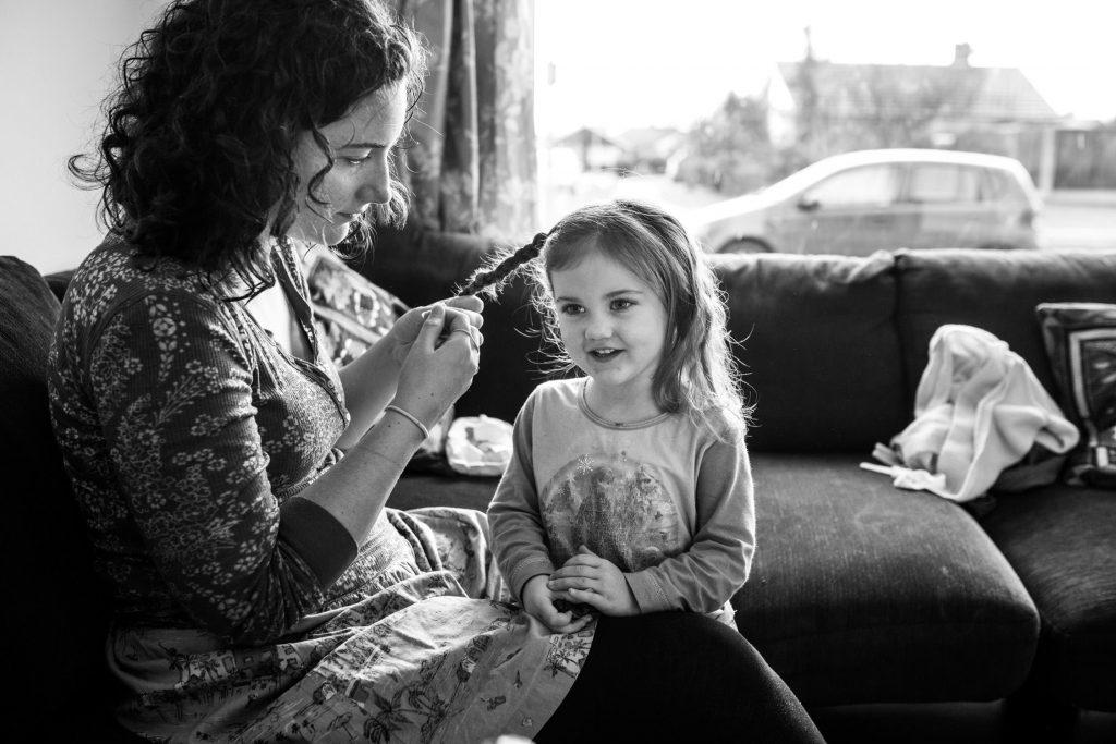 mom braiding her daughter's hair