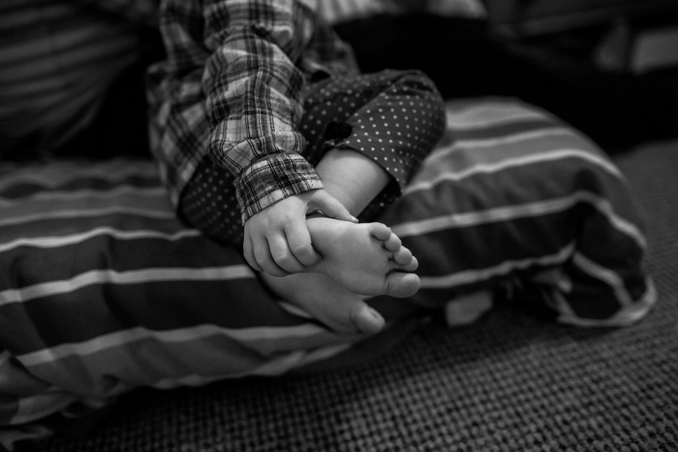 little girl's hand on her small foot