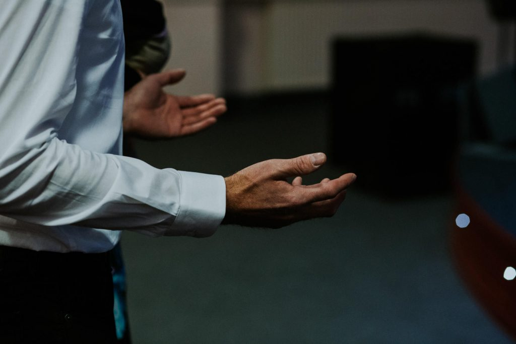 a detail shot of the hands of a man signing worship music during a church service