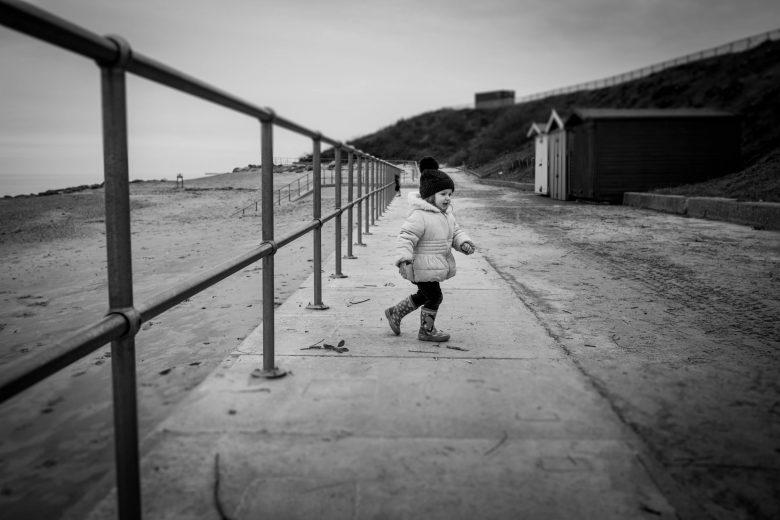 little girl running on the seaside promenade