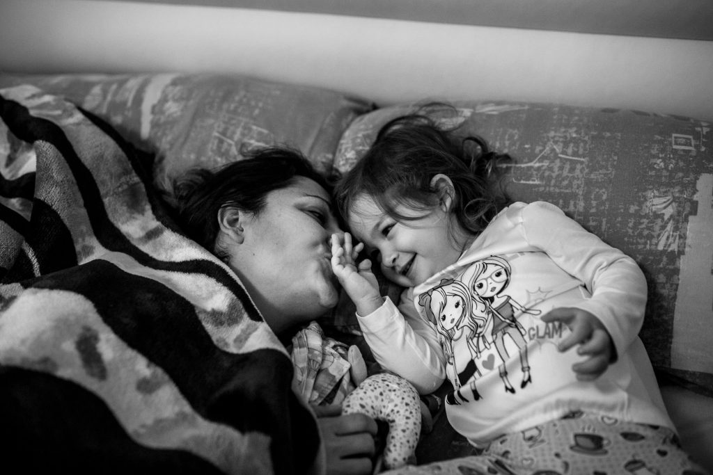 Mother kissing daughter in bed.