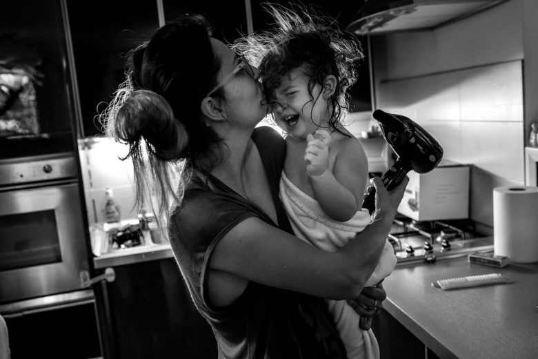 Mother drying daughter's hair and kissing her while the little one is crying.