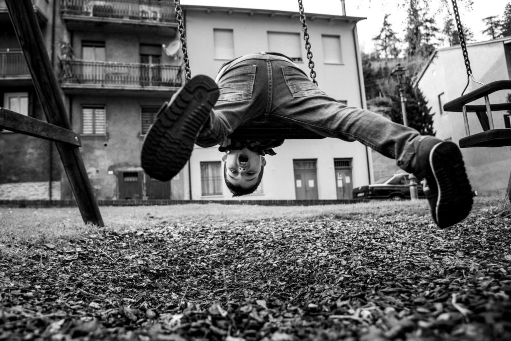 Boy upside down on the swing.