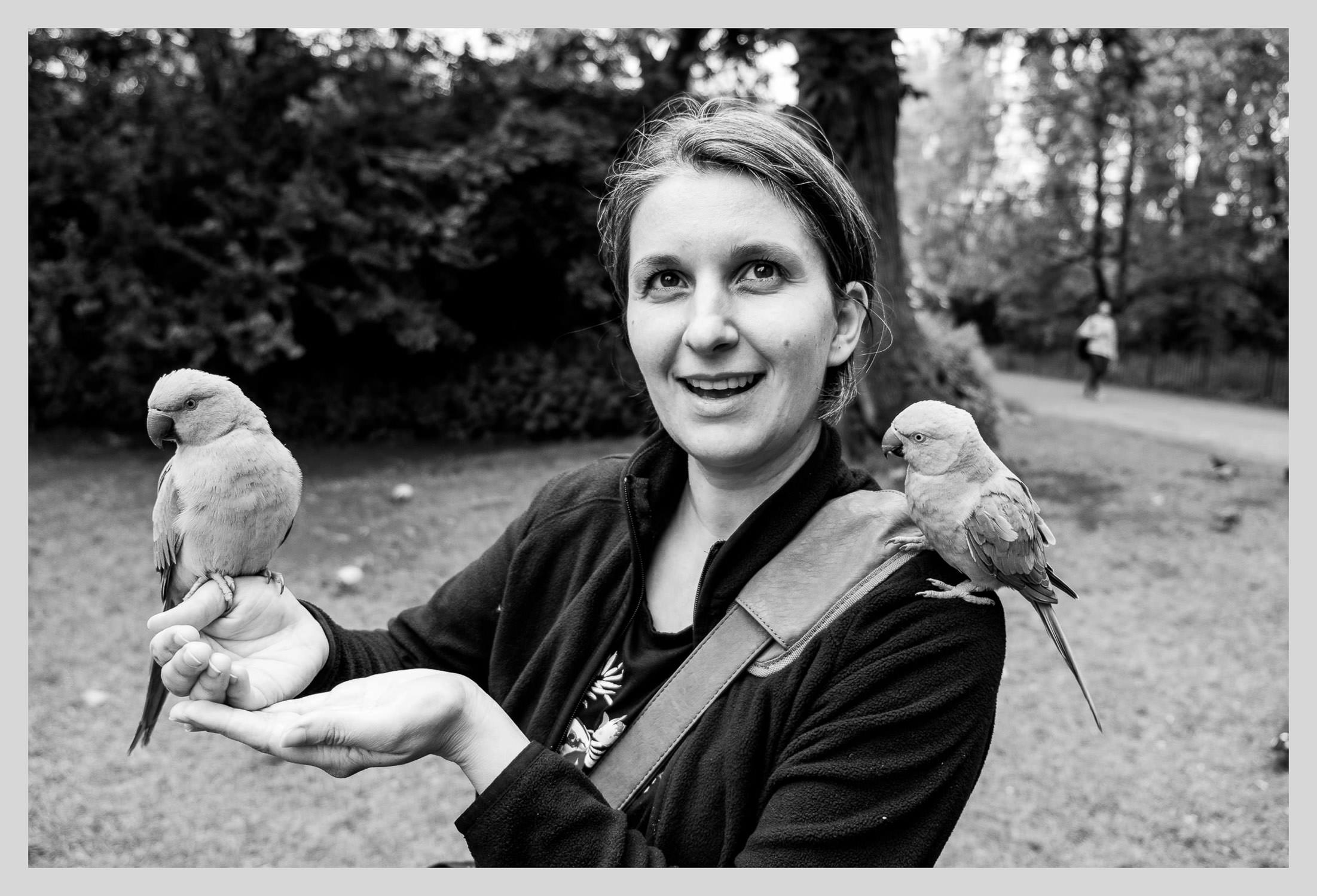 documentary family photographer with parrots on shoulder and hand