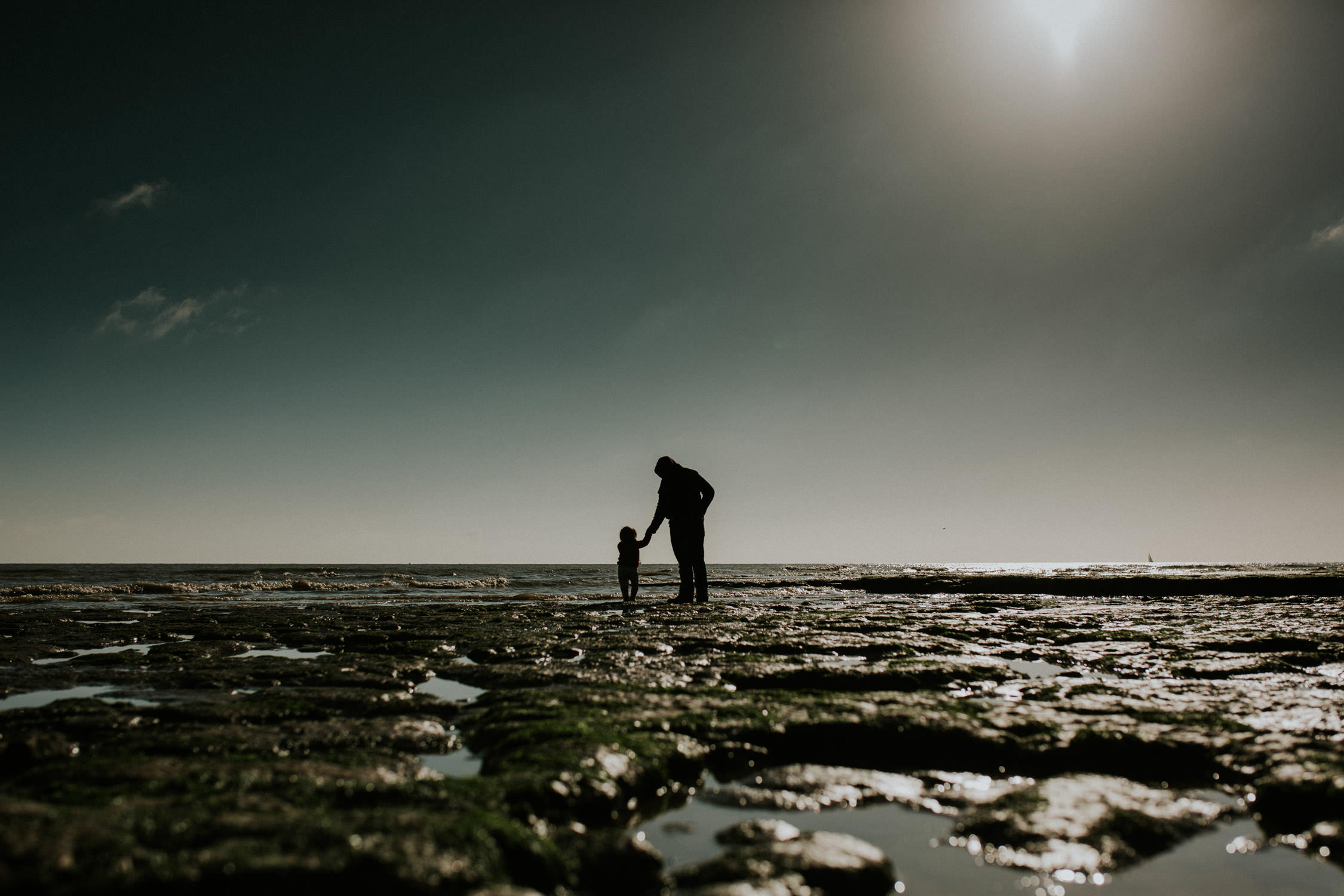 dad and little girl walking towards the sea in walton on the Naze