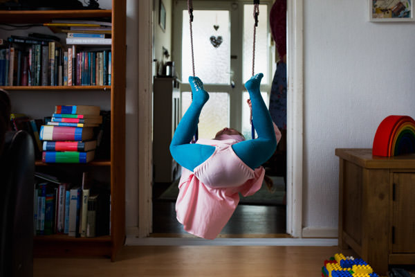little girl upside down on a swing, with a pink outfit and blue leggings.