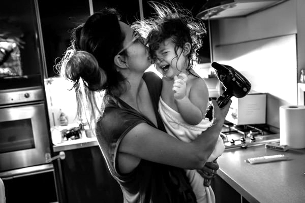 mother kissing crying daughter while she dries her hair after the evening bath.