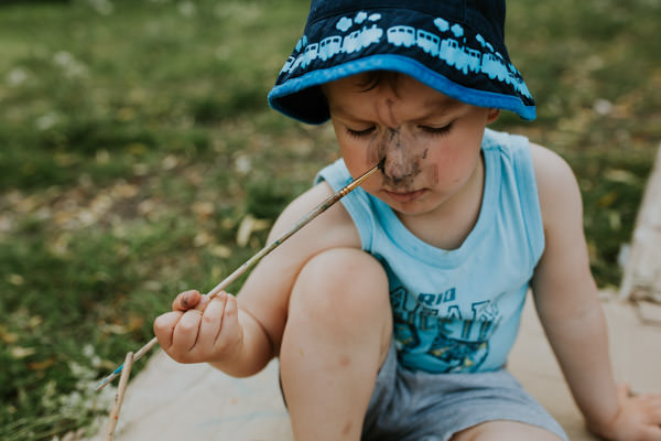 little boy painting his nose