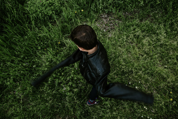 little boy in big leather jacket running on the grass.