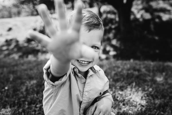 little boy smiling and playfully looking into the photographer's camera and waving his hand.