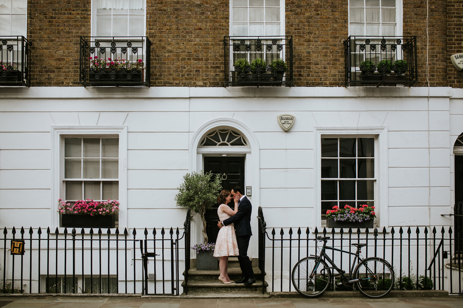Couple kissing in front of a traditional London terrace house