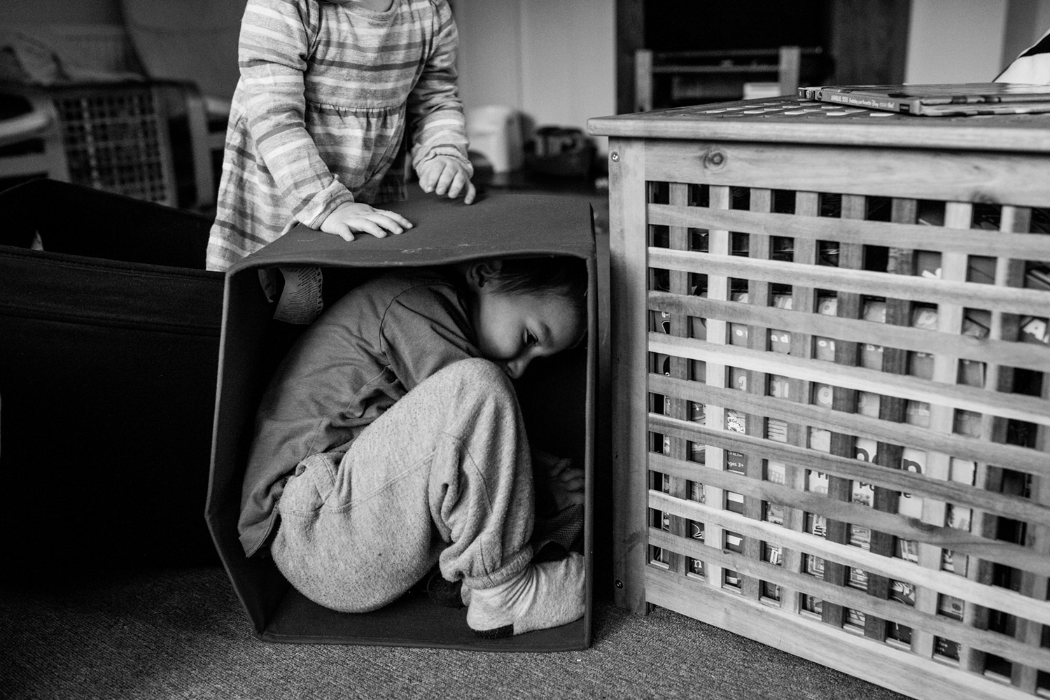 boy trying to fit in a box, on the floor, in an Essex home