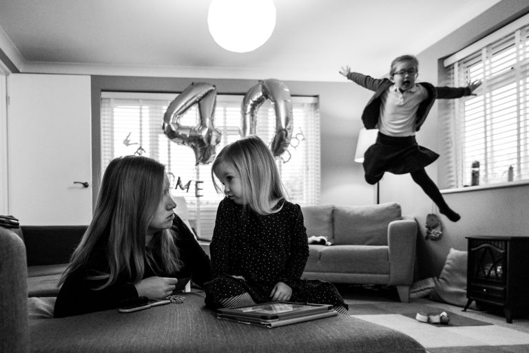 In the foreground, mom and daughter are talking to each other while in the background the sister jumps up in the air. Photographed by ralu Chase photography, an Essex family photographer.