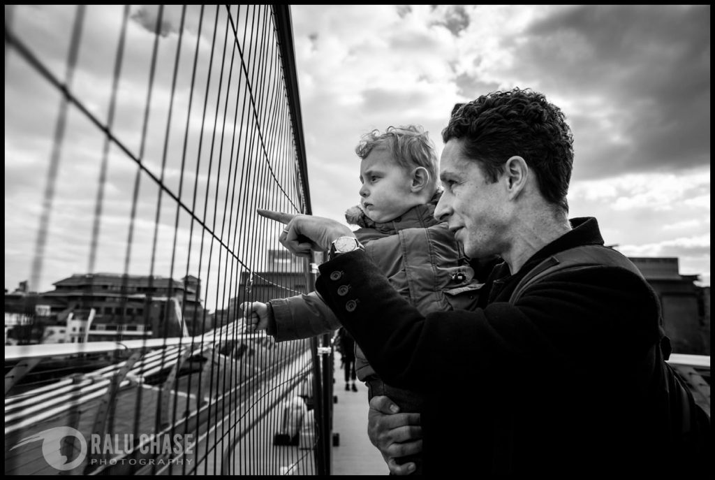 dad and son on Millennium Bridge during a documentary family session in London. The dad is pointing pass the temporary fence, towards the rest of London
