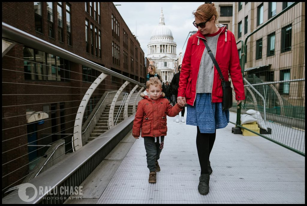 mom and son walking on the Millennium Bridge with St Paul's cathedral in the background. Photograph taken during a London documentary family shoot