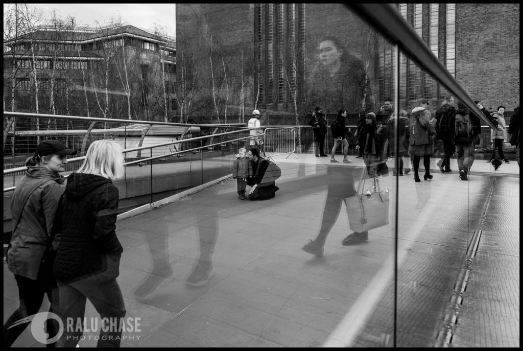 dad is low on the ground, showing his little kid something in the horizon. the photograph is taken on the Millennium Bridge in London by Ralu Chase, a London documentary photographer in London