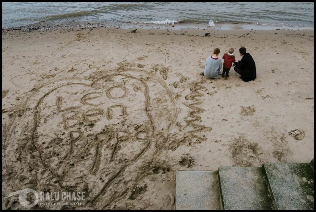 family of three on the south sand banks of the thames looking towards the river. behind them, in the sand, there is a big heart with their names in the middle of it. the photograph is taken by Ralu Chase, a London family photographer