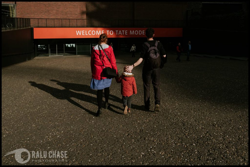 Mom, dad and child walking together towards the entrance of the Tate Modern Museum in London. the dad gently touches the head of the little kid during a London family session.