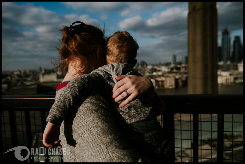 mom holding her son very tight while enjoying the view from the top level of Tate Modern Museum in London