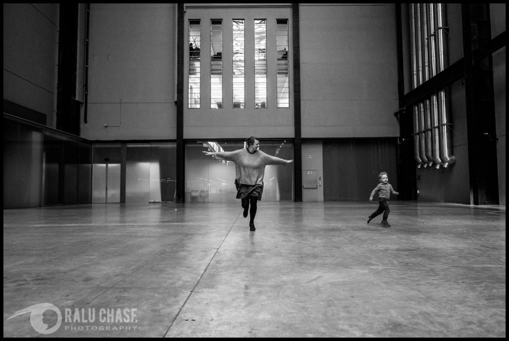 mom and child happily running in the big halls of the Tate Modern Museum in London