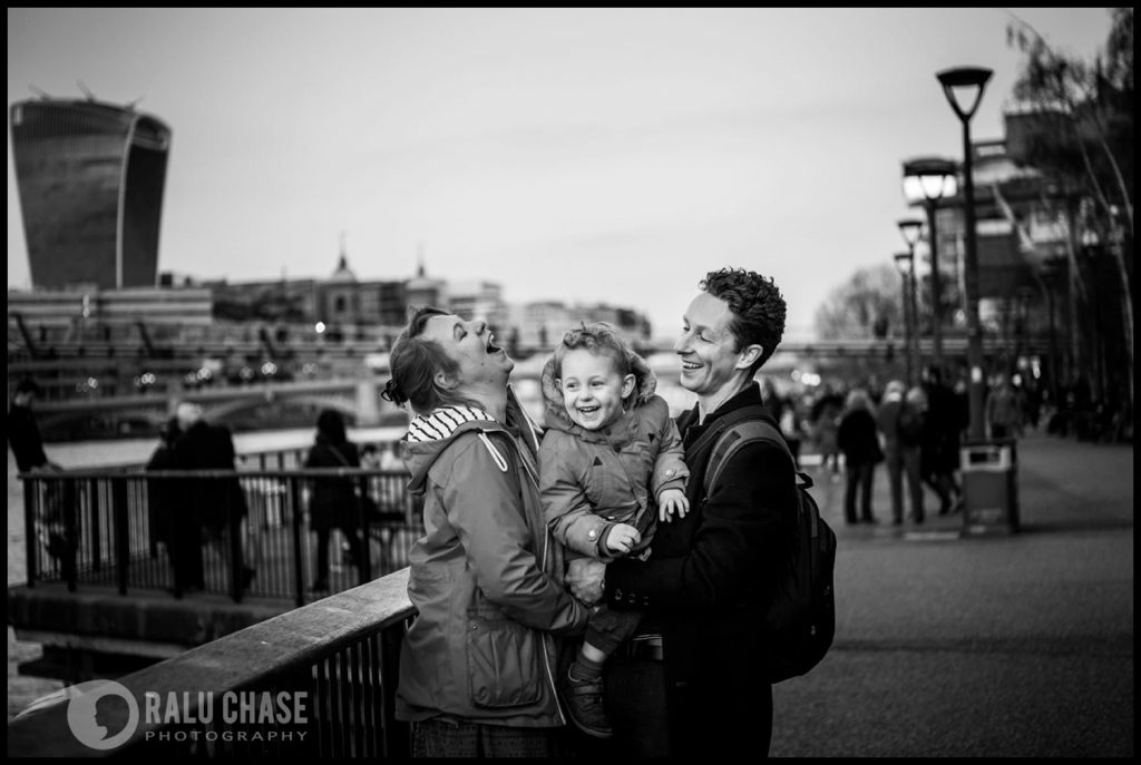 family of three laughing in front of the Tate Modern museum while being photographer by London Family photographer Ralu Chase