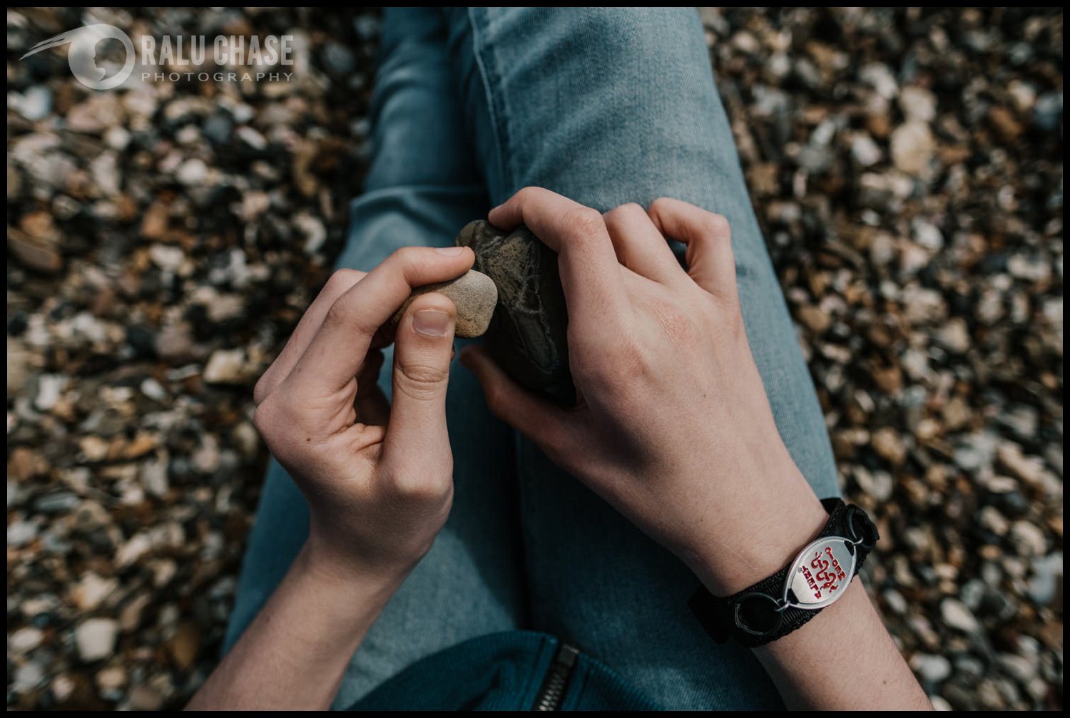 A detail image of the hands of a boy playing with rocks on the beach while wearing a medical alert bracelet. Photograph taken by personal branding photographer, Ralu Chase Photography