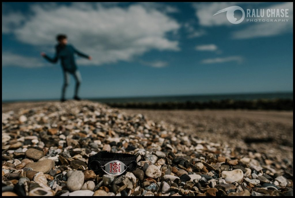 in the foreground there is a medic alert bracelet laying on beach stones. on the background there is a a boy throwing rocks in the water
