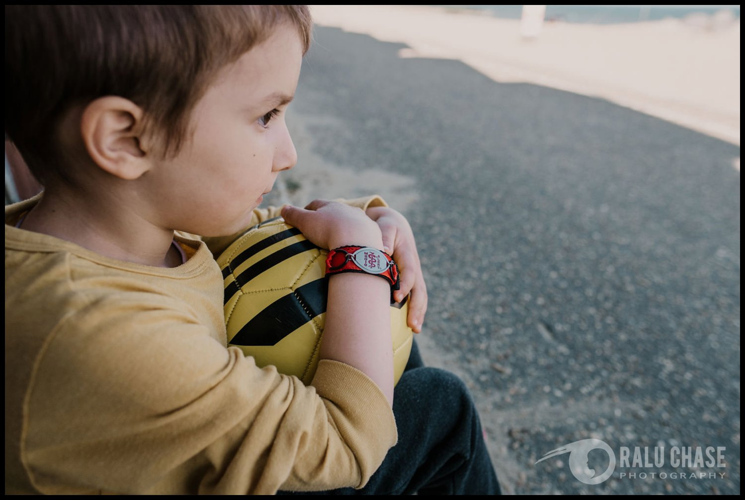 little boy holding tight to a football while wearing a medic alert bracelet. the bracelets have important medical information engraved on them so that people can get quick access to medical help in case of an emergency