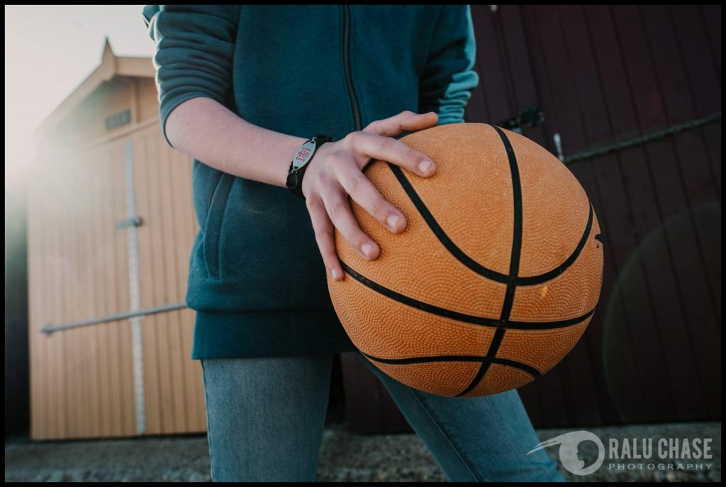 detail branding photography shot of a medic alert bracelet. it is worn by a teenage boy dribbling a basketball