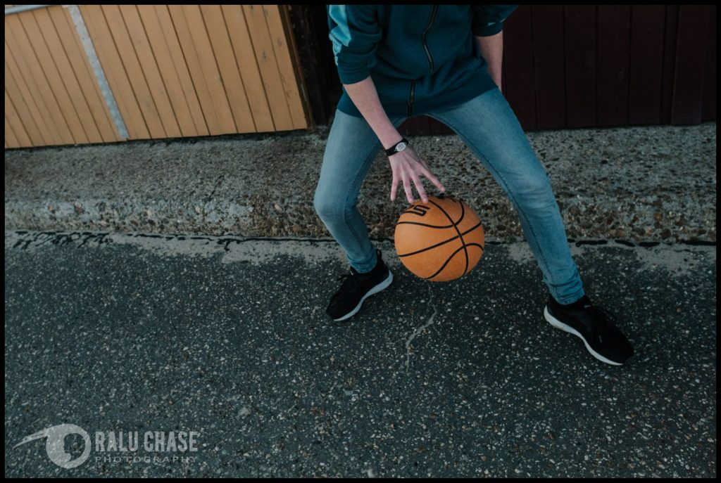 teenage boy wearing next jeans and hoodie dribbling a basketball in front of the holland on sea beach sheds. the photograph is taken during a branding photo session for the medic alert bracelets
