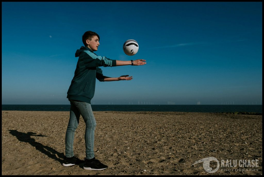 teenage boy wearing a next hoody, playing ball on holland on sea beach. he is wearing a medical ID bracelet made by Medic Alert