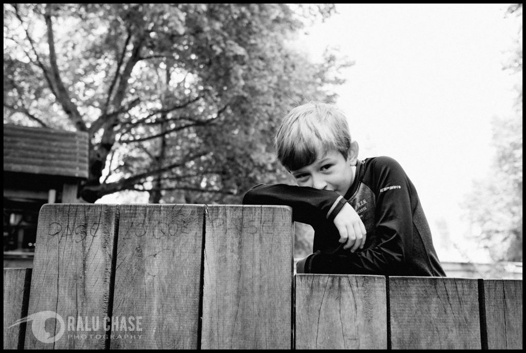 a black and white image of a little boy posing during a family session in Victoria Tower Gardens, near London's Parliament building.