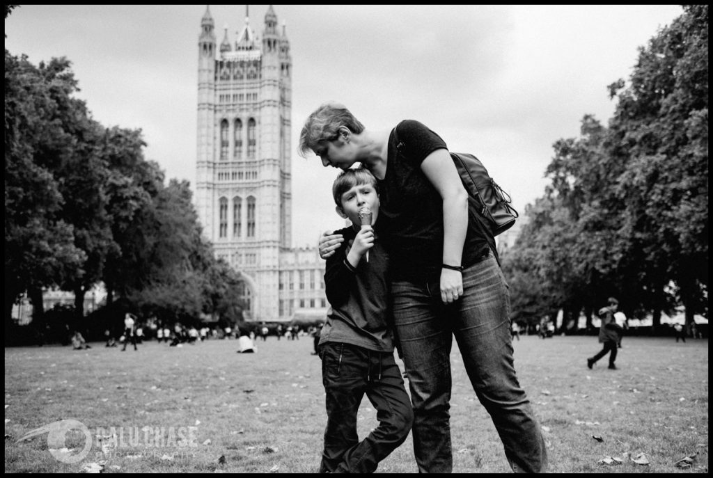 a black and white image of a mother giving her boy a hug. he is eating ice cream while she leans in and hugs him tight in front of London's parliament building