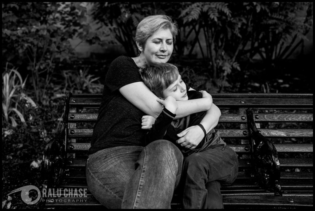 mom and son sitting on a bench in central London. Mom hold the boy really tight while the boy holds onto her. they both have their eyes closed which highlights the strong connection they have.