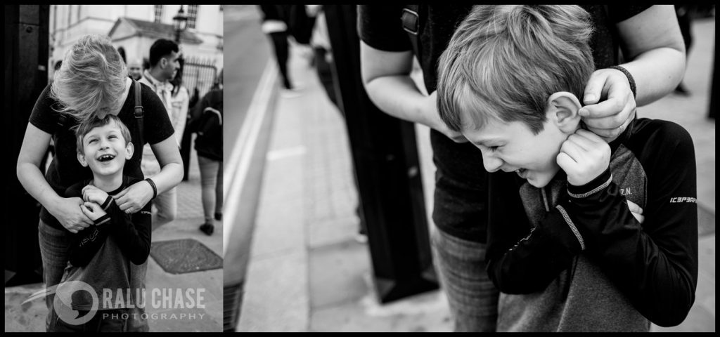 a black and white collection of two photographs with a mom and her son. in one image the mom is kissing her son on the top of his head while waiting to cross at a central London zebra crossing. in the second image the mom is tickling him behind his ears while he is laughing.