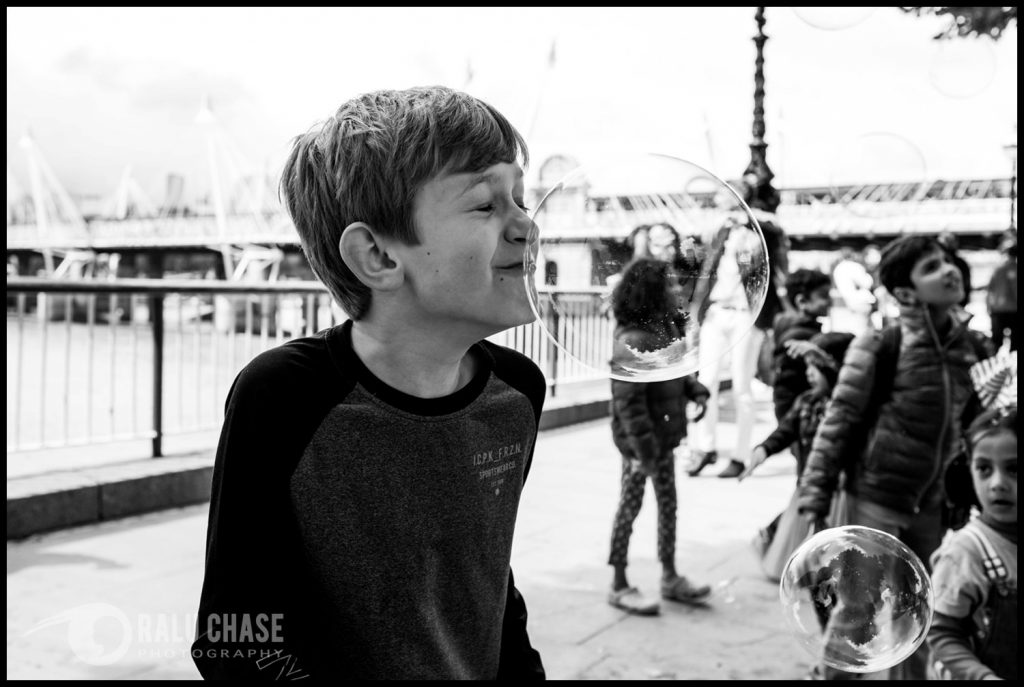 boy trying to pop a soap bubble with his nose. the picture is taken on the Queen's walk, near London Eye, during a family session.