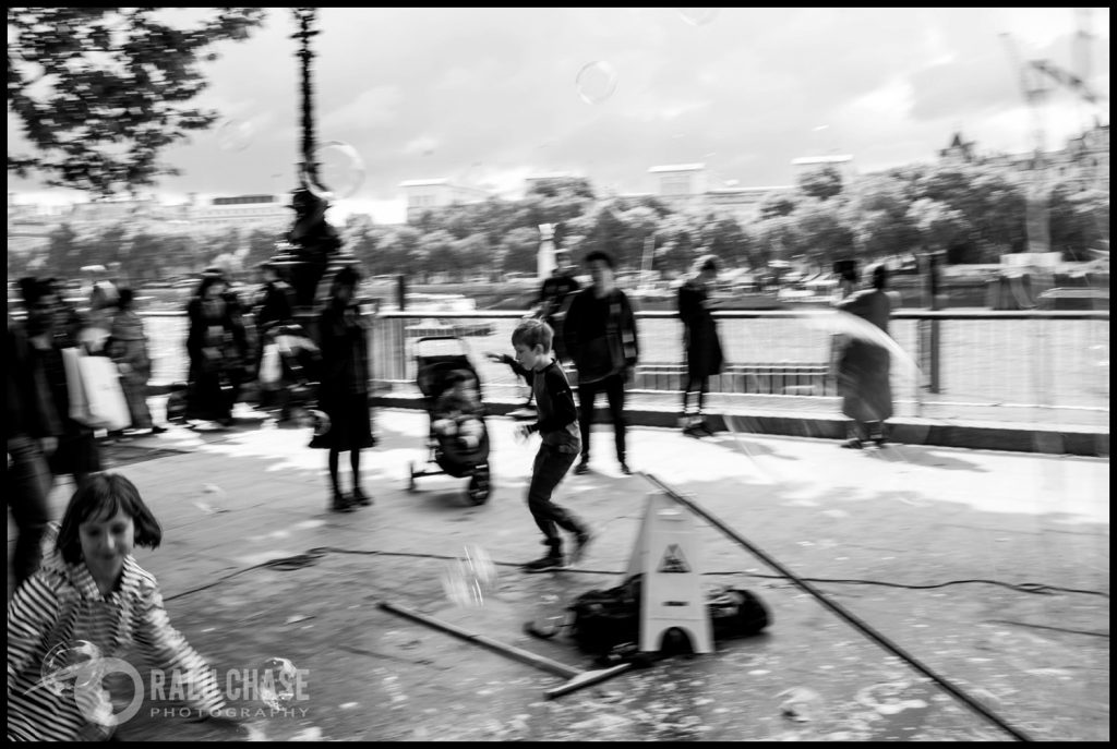 a black and white image of a boy running to try and catch soap bubbles on Queen's Walk, near London Eye.