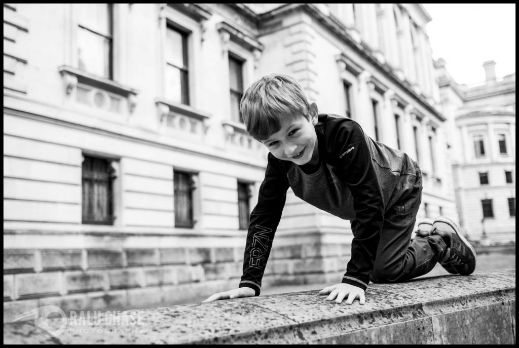 boy climbing on stone walls during a Central London family session
