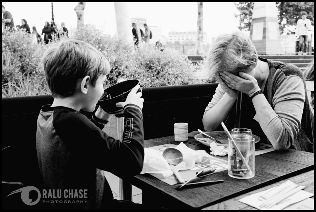 a black and white photograph of mom and son sitting down to have a meal at wagamama's restaurant in Central London. Mom holds her face in her palms while the boy is drinking his soup instead of using his utensils to eat it.