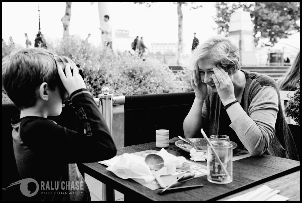 a black and white photograph of mom and son sitting down to have a meal at wagamama's restaurant in Central London. Mom is holding her head and laughing at her boy's decision to drink his soup instead of using his utensils to eat it. the soup bowl is covering the boy's face.