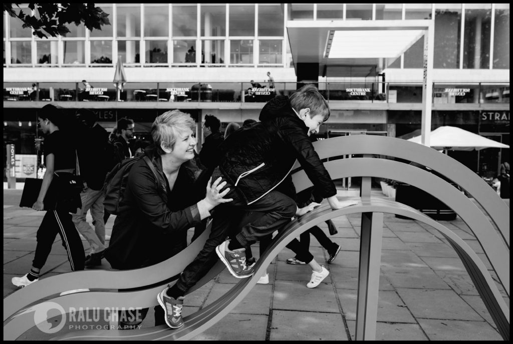 mom pushing her son on one of the art instalments near London Eye. The photograph is taken during a family photo session on a windy summer day in London, by Ralu Chase - a London family photographer