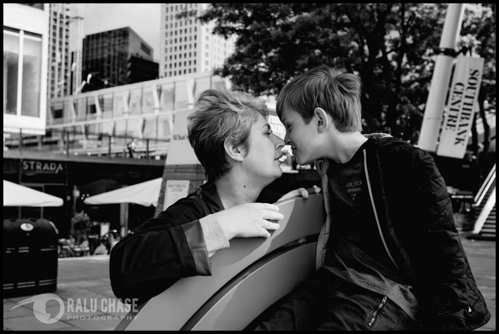 mom and son touching noses near southbank center in London. The photo is black and white and it's taken by Ralu Chase - a London documentary family photographer