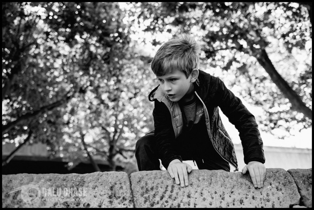 boy climbing over rocks on southbank London