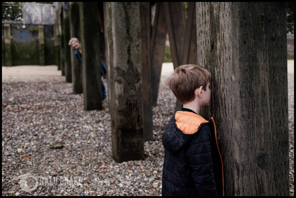 little boy counting to 10 while playing hide and seek with his mom. the boy is in the foreground, while the mom is far in the background, poking her head out from her hiding place while waiting for him to finish his counting. the photograph is taken in Central London during a family session