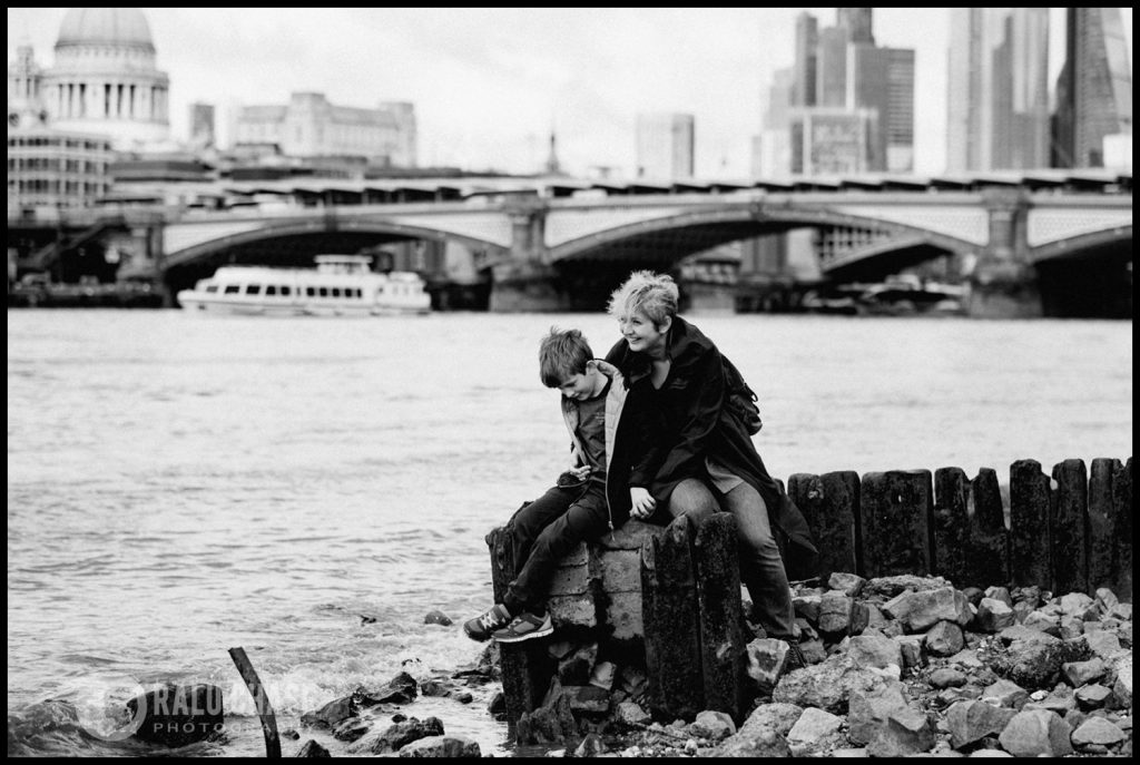 mom and son sitting on the ruins of a small board walk on the south bank of the Thame's river. the photograph is taken by Ralu Chase - a London family photographer